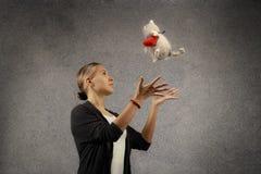 Dosyć szczęśliwa młoda blond kobieta w przypadkowych płótnach łapie pluszową kot zabawkę z sercem, marzący, przyglądający up Zdjęcia Royalty Free