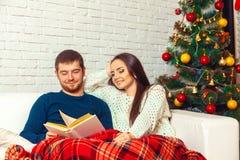 Dosyć szczęśliwa para w miłości czyta boże narodzenia czarodziejski ogon na couc Obrazy Stock