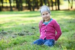 Dosyć szczęśliwy dziewczyna portret, siedzi dalej klęczy na trawie, copyspace Zdjęcia Royalty Free