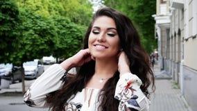 Dosyć szczęśliwy kobieta uśmiech i pozować kamera na ulicie zbiory