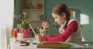 Dosyć trochę szkolny dzieciak chce robić pracie domowej na pastylce przy stołem na słonecznym dniu w domu zbiory