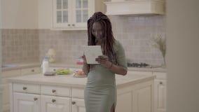 Dosyć uśmiechać się amerykanin afrykańskiego pochodzenia kobiety stoi w kuchni z pastylką w rękach z dreadlocks Dama nabywał zbiory