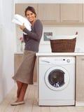 Dosyć uśmiechać się dziewczyny w pralnianym pokoju Fotografia Stock