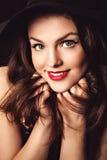 Dosyć uśmiechać się kobiety w eleganckim czarnym kapeluszu Obrazy Royalty Free