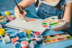 Dosyć uśmiechać się młodej kobiety rysuje obrazek z plakatową farbą zdjęcie royalty free