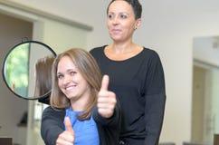 Dosyć uśmiechać się 20s kobiety przy fryzjerami Zdjęcia Stock