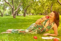 Dosyć uśmiechać się szczęśliwej dziewczyny w zieleni sukni czytelniczej książce i lying on the beach na trawie zdjęcia royalty free