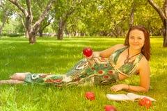 Dosyć uśmiechać się szczęśliwej dziewczyny w zieleni sukni czytelniczej książce i lying on the beach na trawie obraz stock