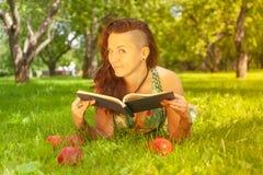 Dosyć uśmiechać się szczęśliwej dziewczyny w zieleni sukni czytelniczej książce i lying on the beach na trawie zdjęcia stock