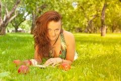 Dosyć uśmiechać się szczęśliwej dziewczyny w zieleni sukni czytelniczej książce i lying on the beach na trawie zdjęcie royalty free