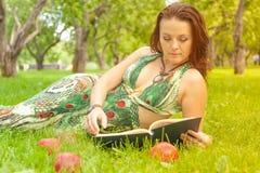 Dosyć uśmiechać się szczęśliwej dziewczyny w zieleni sukni czytelniczej książce i lying on the beach na trawie obrazy stock