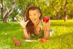 Dosyć uśmiechać się szczęśliwej dziewczyny w zieleni sukni czytelniczej książce i lying on the beach na trawie obrazy royalty free