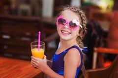 Dosyć uśmiechający się dziecko dziewczyny w okularach przeciwsłonecznych pije w prętowym soku od szkła Obraz Royalty Free
