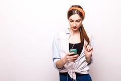 Dosyć uśmiechający się dziewczyny słucha muzycznych jest ubranym hełmofony trzyma wewnątrz rękę telefon Obrazy Royalty Free