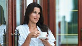 Dosyć uśmiechający się kobiety ma plenerową pije gorącą kawę trzyma rękami herbaty lub filiżankę i spodeczek zbiory
