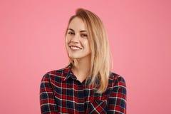 Dosyć urocza kobieta z przyjemnymi uśmiechów spojrzeniami bezpośrednio w kamerę, ubierającą w w kratkę koszula, odizolowywającej  Fotografia Stock