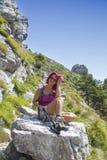 Dosyć w średnim wieku żeński wycieczkowicz odpoczywa na dużej skale zdjęcie royalty free