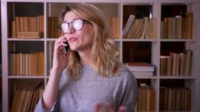 Dosyć w średnim wieku blondynka nauczyciel ma voicecall na smartphone jest radosny i uradowany przy biblioteką zbiory