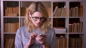 Dosy? w ?rednim wieku blondynka nauczyciel ogl?da attentively w smartphone koncentruje przy bibliotek? zbiory wideo