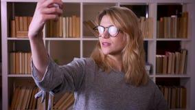 Dosy? w ?rednim wieku blondynka nauczyciel w szk?ach robi selfies u?ywa? smartphone przy bibliotek? zbiory wideo