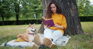 Dosyć z włosami dziewczyna ucznia czytelniczej książki obsiadanie w parku na gazonie z psem zbiory wideo