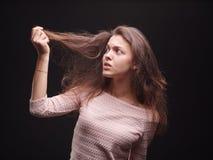 Dosyć, zmartwionej damy wzruszający włosy na czarnym tle Młoda kobieta rozczarowywająca z jej włosy Kruchy włosiany pojęcie Zdjęcie Stock