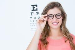 Dosyć geeky modniś z szkłami i oko testem Zdjęcia Royalty Free