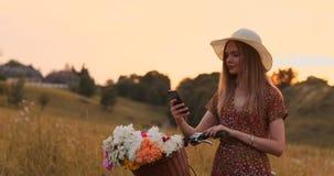 Dosy? ?liczna dziewczyna u?ywa smartphone obok jej roweru w parku z palmami na s?onecznym dniu ?adna dziewczyna u?ywa smartphone zdjęcie wideo