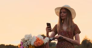 Dosy? ?liczna dziewczyna u?ywa smartphone obok jej roweru w parku z palmami na s?onecznym dniu ?adna dziewczyna u?ywa smartphone zbiory