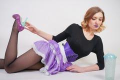 Dosy? modna blondynki dziewczyna jest ubranym czarnego kombinezon z siatki pantyhose i purpura gorsecikiem na bia?ym tle zdjęcia stock