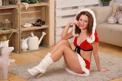 Dosyć seksowna kobieta jest ubranym Święty Mikołaj odziewa, siedzący na ciepłym dywaniku Obrazy Royalty Free