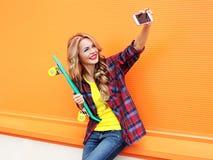 Dosyć uśmiechać się blondynki młodej kobiety w kolorowych ubraniach z łyżwą Obraz Stock
