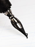 Dot letter I with metal nib. Of drawing pen by black ink close up Stock Photo
