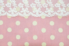Dot pattern and lace on pink fabric texture. Stock Image