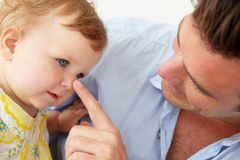 Doting father with baby daughter at home. Playing stock image
