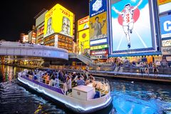 Dotonbori Canal Osaka. Osaka, Japan - April 29, 2017: touristic boat in Dotonbori Canal and famous Glico Running Man sign in Dotonbori street, Namba, a popular Royalty Free Stock Image