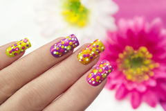 Dots. Colour nail Polish are covered with yellow,purple,pink,green lacquer and gold sparkles in the form of points Royalty Free Stock Images