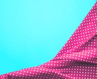 Dots pink fabric cloth with blue background. Royalty Free Stock Photo