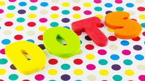 Dots and polka dots. Colorful foam letters spelling dots on bright polka dot background royalty free stock photo
