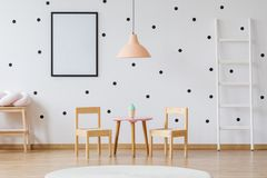 Dots wallpaper and wooden furniture. Dots wallpaper and wooden small size furniture in playing room royalty free stock image