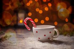 Dotted china cup. With candy cane on Christmas style background Stock Images