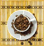 Dotted cup filled with coffee beans standing on a plate Stock Photos