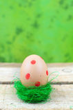Dotted easter egg in nest. Easter egg with red dots in nest on green background Stock Image