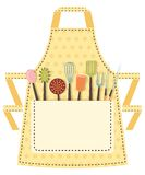 Dotted kitchen apron with kitchen utensils in the Royalty Free Stock Image