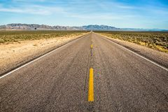 Dotted line down long, straight, Extraterrestrial Highway of the Nevada Desert. Yellow dotted line down the long, straight highway through the Nevada desert. The stock photos