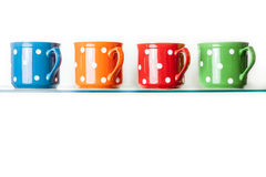 Dotted mugs in various colors on white Stock Image