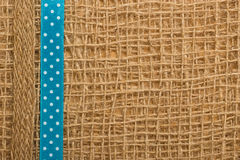 Dotted ribbon on burlap cloth background Royalty Free Stock Photos