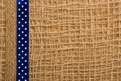 Dotted ribbon on burlap cloth background Stock Image