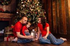 Dotter för pappa` som s ut blåser stearinljus på en julgran arkivfoton