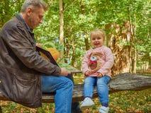 Dotter fader, barn, bok, hem, barn, farsa, härligt som sitter, man, familjbarnuppfostran som är gullig, läsning, lite, tillsamman Arkivbild